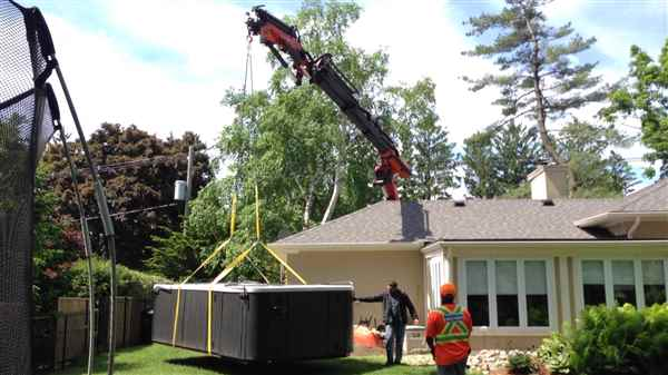 Craning a 4000 pound swim spa around a house.