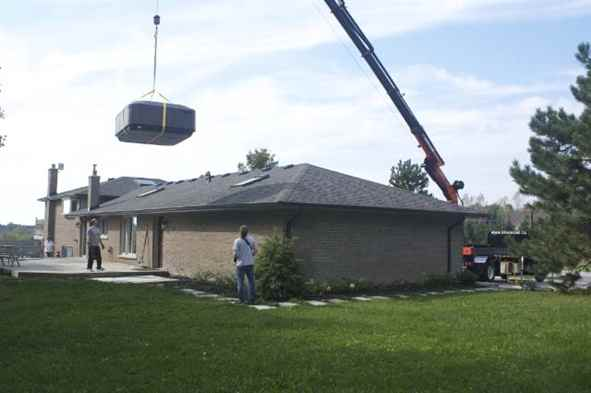 Craning hot tub over house.