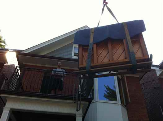 Craning an upright piano onto a balcony.