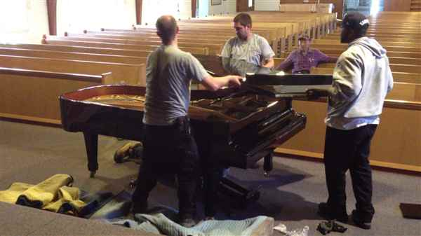 Attaching back a grand piano lid onto a grand piano in a church