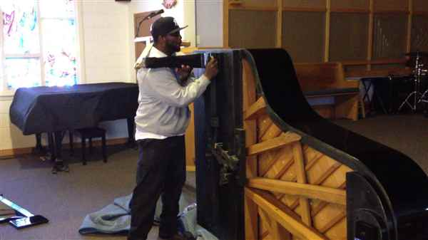 Attaching a grand piano leg onto a grand piano.