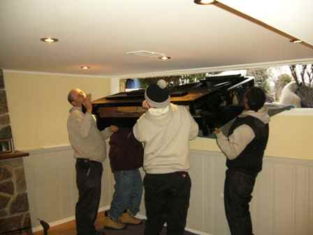 Lifting a grand piano through a basement window.