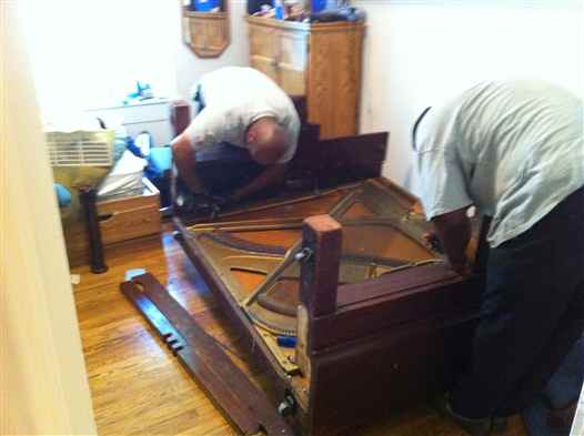 Taking apart an upright piano so that it will fit down the stairs.
