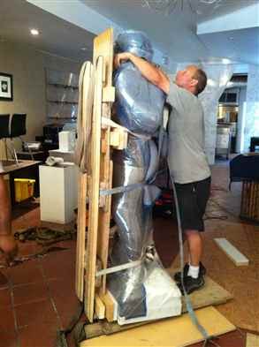 Preparing a marble statue which has to go down a flight of stairs outside.