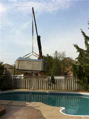 Crane hot tub over pool
