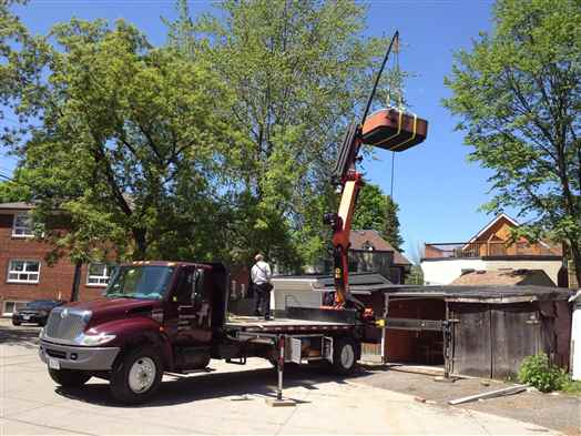 Craning a hot tub out of a backyard.