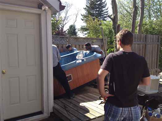 Positioning a hot tub on a backyard deck.