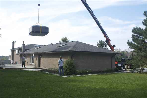 Craning a hot tub over a house.