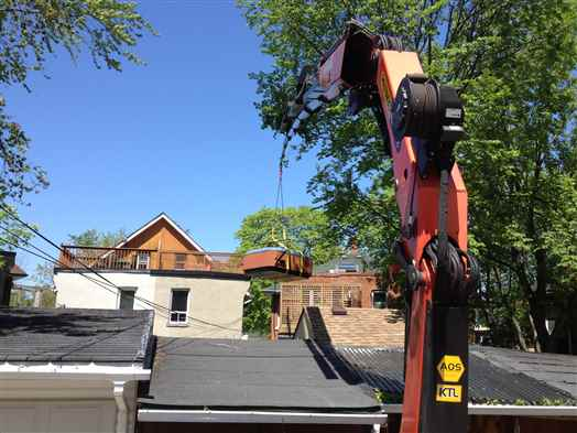 Craning a hot tub off a third floor deck.