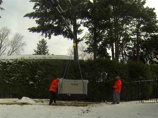 Craning a heavy generator over the snow into a backyard.