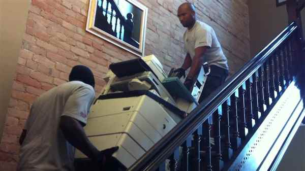 Moving a photocopier down a flight of stairs.