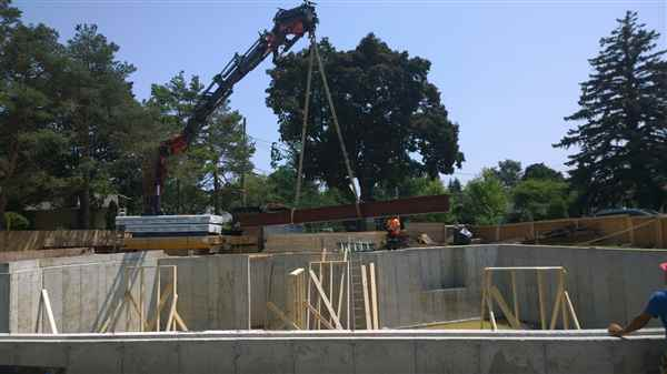 Crane beam into place on construction site.